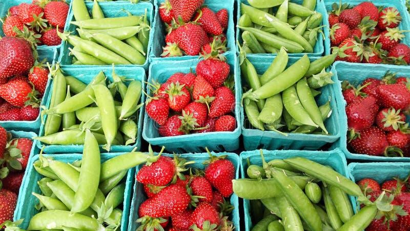 Pois et fraises de ressort au marché d'agriculteurs images stock