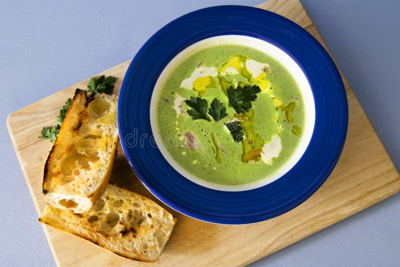 Pois et Ham Soup avec de la crème et la baguette sur le conseil rustique photos libres de droits