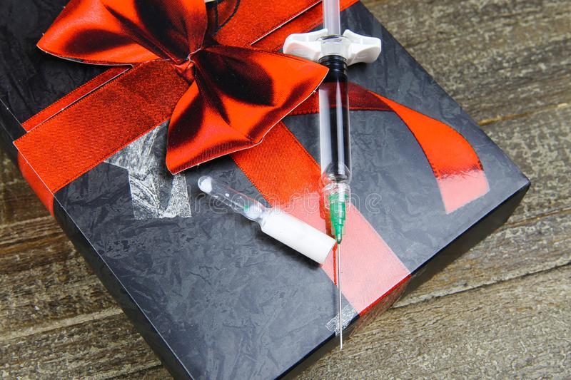Poisoned chalice gift symbol concept: isolated syringe with injection needle and vial with white fluid on present box on wood stock image
