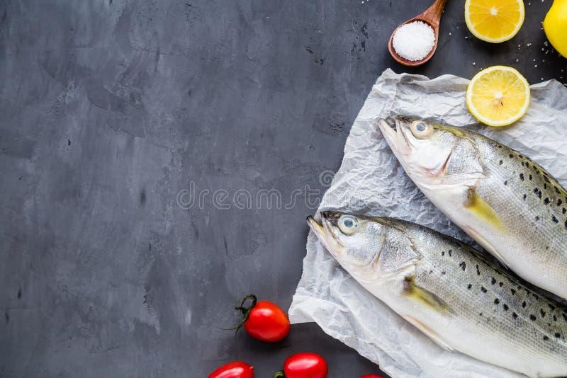 Poisson cru frais avec des épices, citron, sel sur le fond en pierre foncé Disposition créative faite de poissons, vue supérieure photos libres de droits