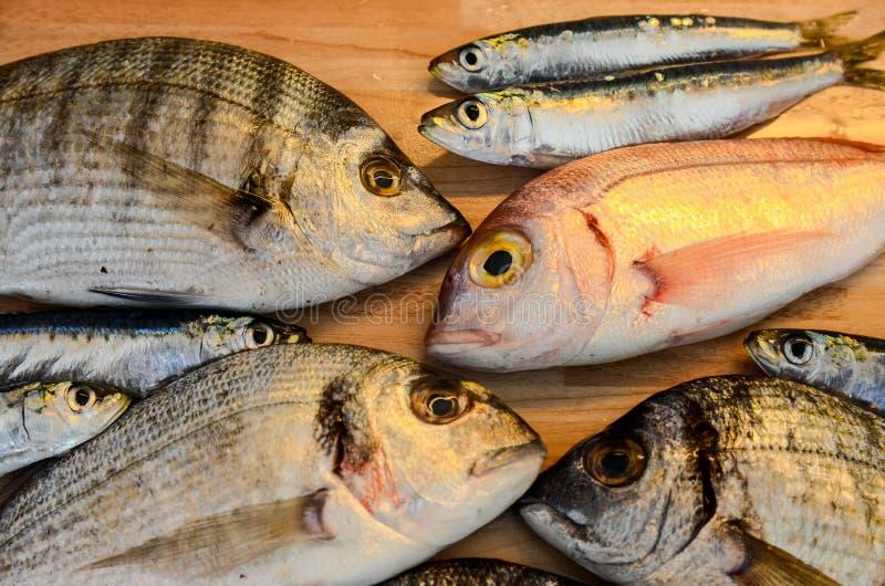 Poisson frais avec le citron prêt pour la cuisson Préparation du repas délicieux et savoureux de fruits de mer Dorade tête jeune  photos libres de droits