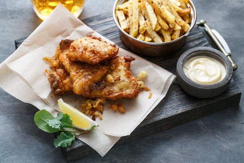 Poisson-frites traditionnels britanniques avec de la sauce à tartre sur le papier chiffonné photos stock