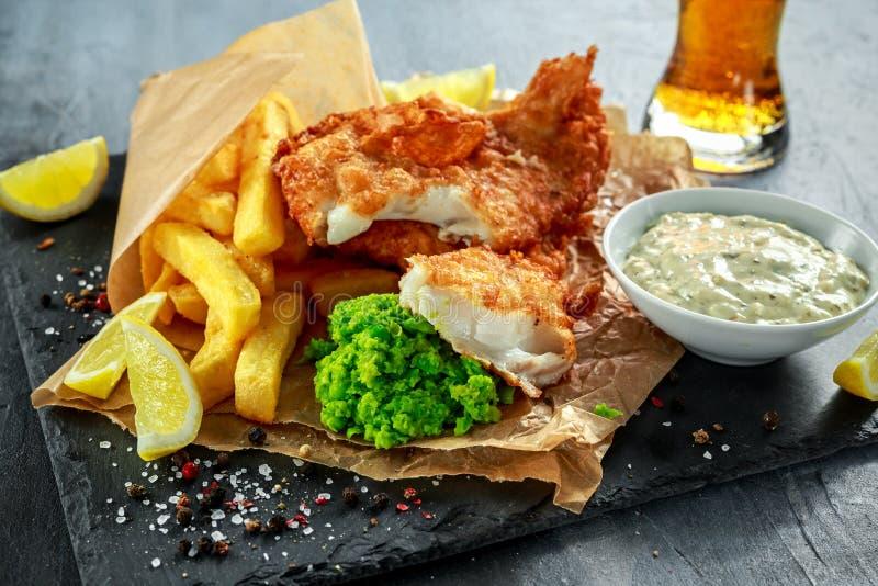 Poisson-frites traditionnels britanniques avec les pois écrasés, sauce à tartre sur le papier chiffonné avec de la bière froide photo stock