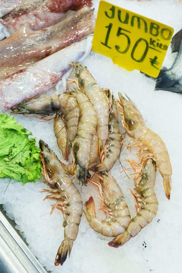 Poissons, crevette et poulpe effrayants frais de fruits de mer sur la glace au compteur de poissonnerie photographie stock