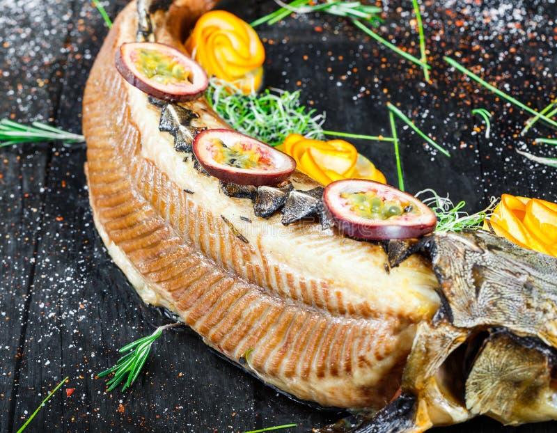Poissons cuits au four d'esturgeon avec le romarin, le citron et la passiflore comestible de passiflore du plat sur la fin en boi photographie stock libre de droits