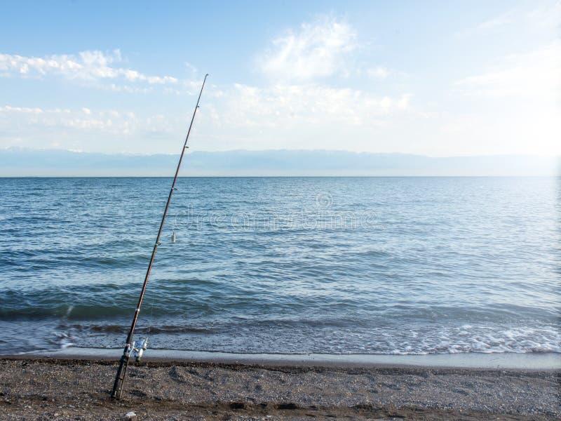 Poissons de pêcheur tôt le matin sur le rivage Canne à pêche et rotation camper photos libres de droits