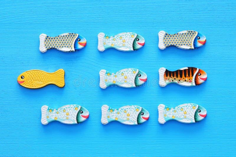 poissons différents nageant vis-à-vis de la manière de l'identique Concept de courage et de succès images stock
