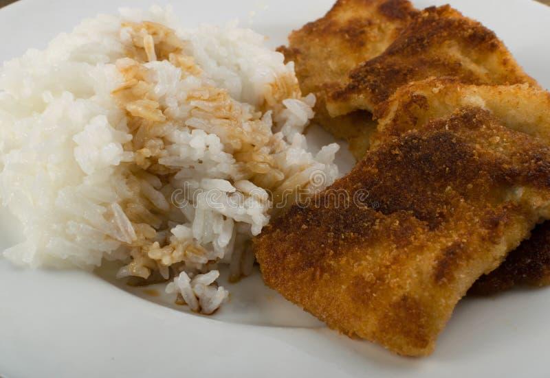 Poissons en chapelure et riz photographie stock