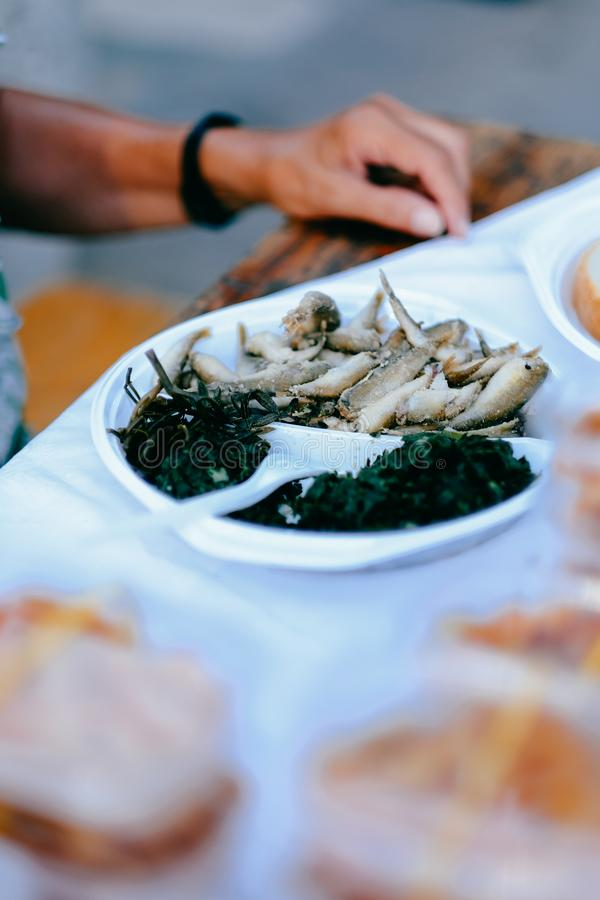 Poissons frais et frits de sardine dans un plat avec de la salade végétale verte photo libre de droits