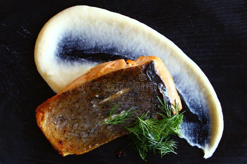 Poissons frits délicieux avec de la purée de pommes de terre et de la verdure sur le fond noir photos libres de droits