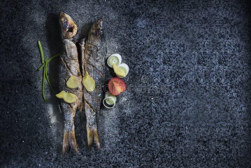 Poissons grillés avec des épices, des légumes et des herbes sur le fond d'ardoise prêt pour la consommation photos stock