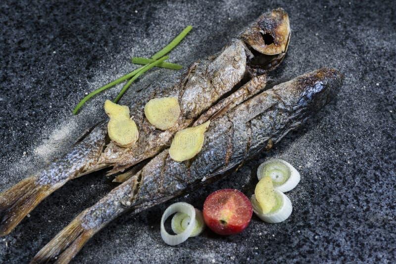 Poissons grillés avec des épices, des légumes et des herbes sur le fond d'ardoise prêt pour la consommation photo stock