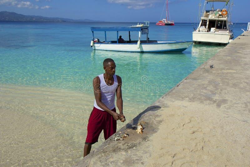 Poissons locaux de coupe d'homme dans Cove Beach de docteur Jamaïque, des Caraïbes photo libre de droits