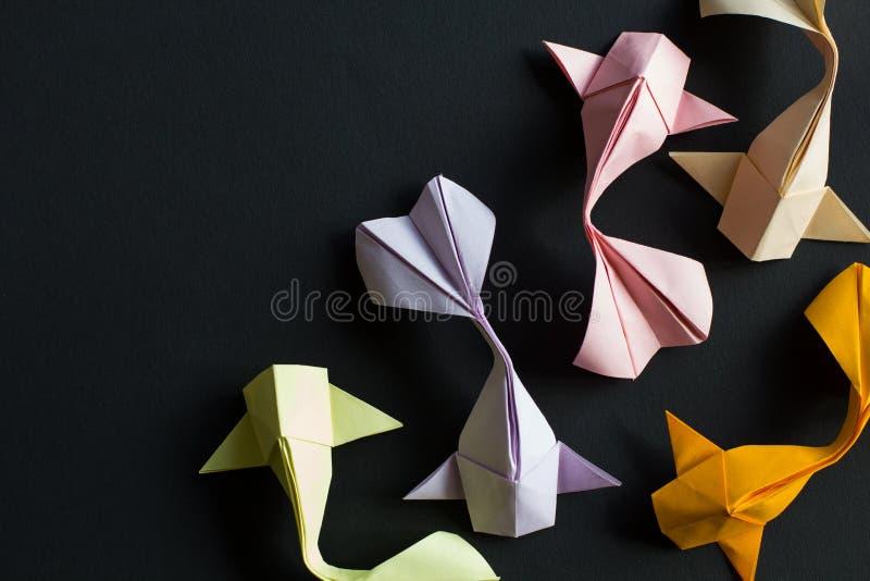 Poissons roses jaunes faits main de carpe de koi d'or d'origami de métier de papier sur le fond noir dans le bon coin Vue sup?rie photos libres de droits