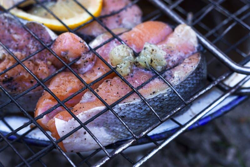 Poissons sur le gril dans le gril Saison de gril Saumons sur le feu images stock