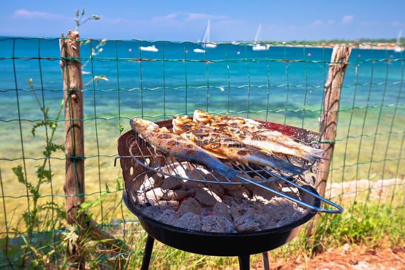 Poissons sur le gril par la plage méditerranéenne, préparation idyllique de nourriture de vacances photo libre de droits