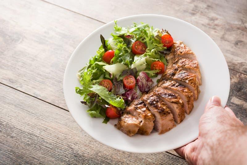 Poitrine de poulet grillée avec des légumes sur une assiette de bois photos libres de droits