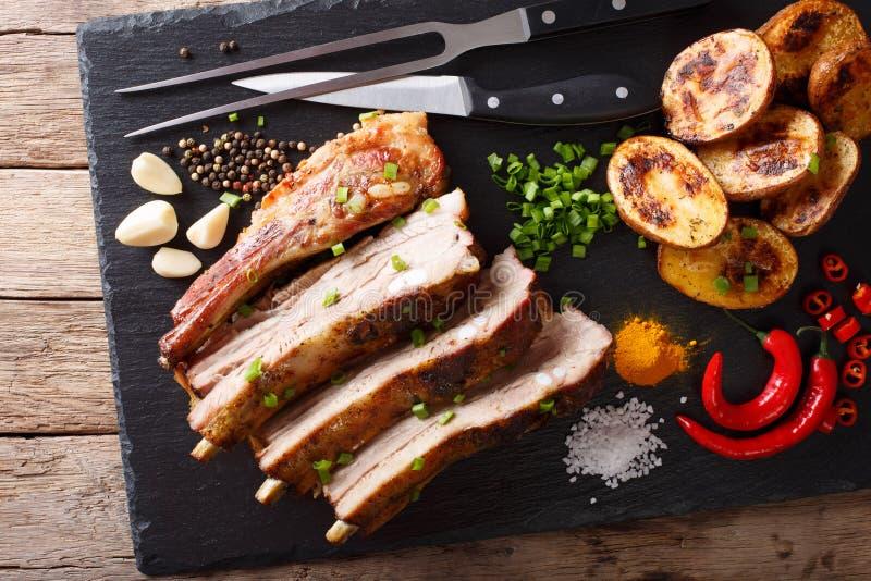 Poitrine faite maison frite de porc avec les pommes de terre cuites au four en gros plan sur ventres images libres de droits