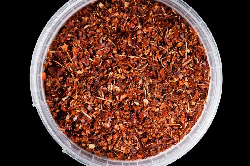 Poivre d'un rouge ardent avec des graines pour assaisonner dans un seau en plastique pour le stockage sur un fond noir, isolat photographie stock