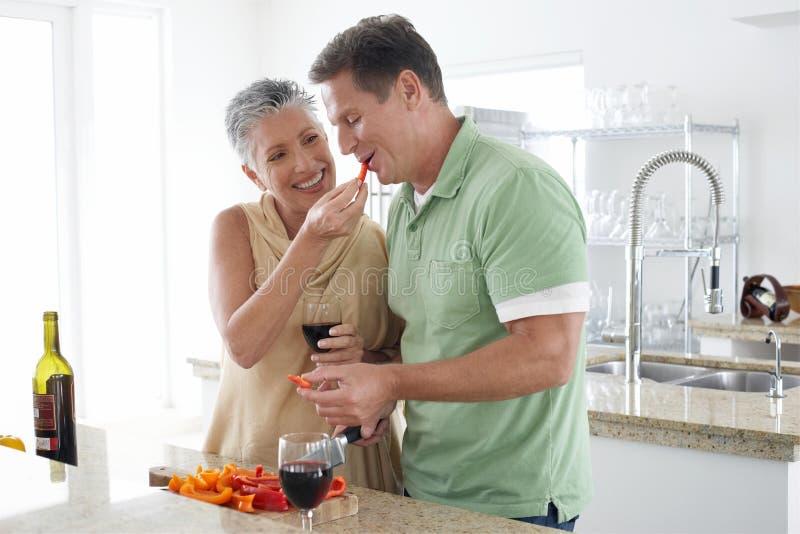 Poivre de alimentation de femme à l'homme dans la cuisine image libre de droits