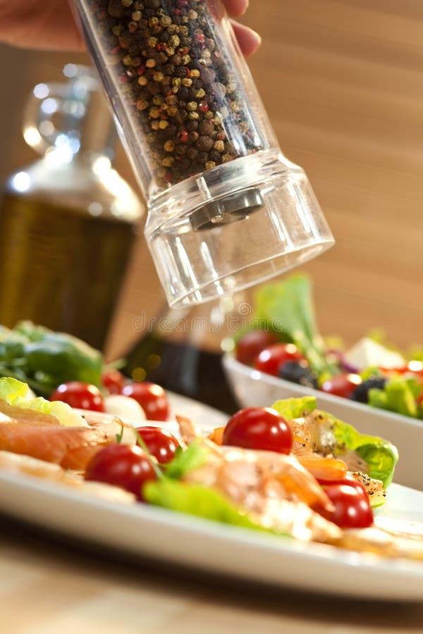 Poivre de meulage sur la salade de fruits de mer image libre de droits