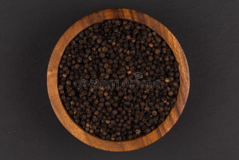 Poivre noir dans la cuvette en bois image stock