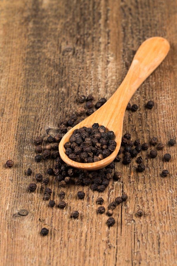 Poivre noir sur la cuillère en bois photos stock