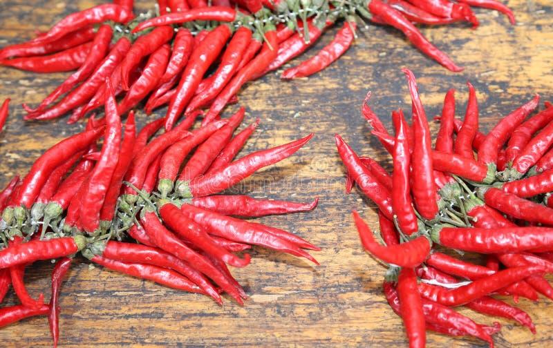 Poivrons d'un rouge ardent sur la table en bois au marché photo stock