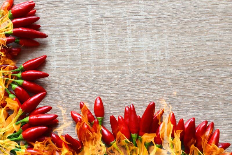 Poivrons de piment d'un rouge ardent avec des flammes du feu photo stock