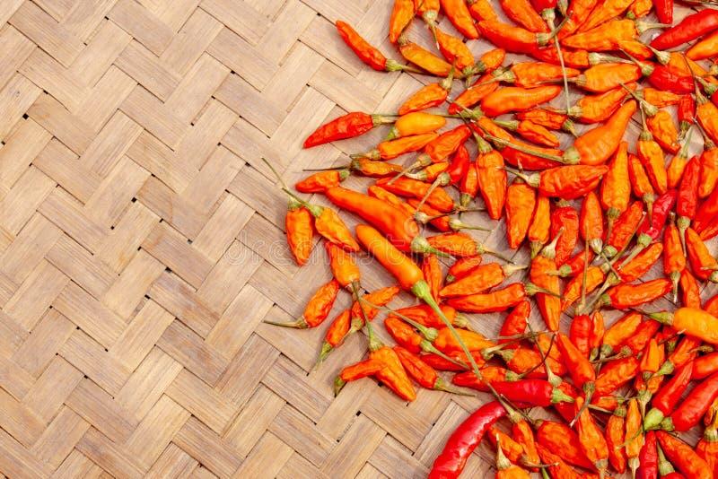 Poivrons de piment rouge secs sur la texture en bambou d'armure photo stock