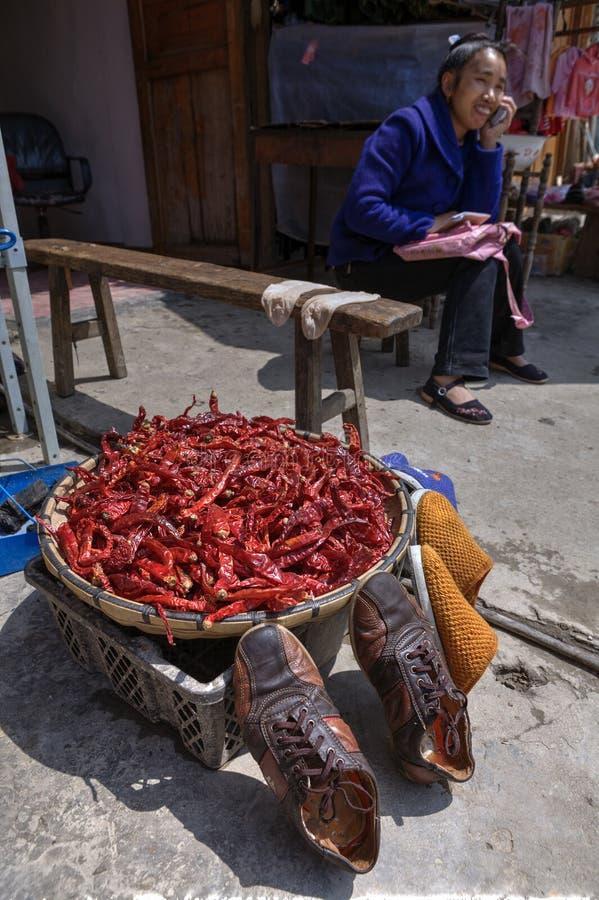 Poivrons de piment séchant à côté de la chaussure, dans le village chinois de minorité photos stock