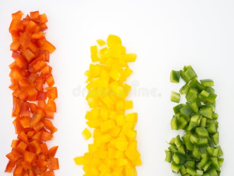 Poivrons doux rouges, verts et jaunes coupés sur fond blanc image stock