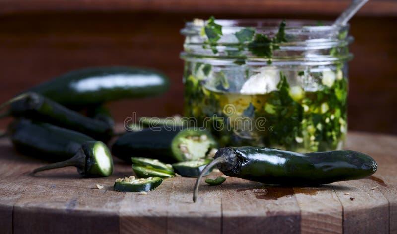 Poivrons et sauces de piment frais chauds sur la planche à découper en bois photographie stock libre de droits