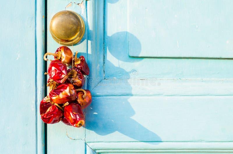 Poivrons secs d'un rouge ardent accrochant sur une porte photographie stock