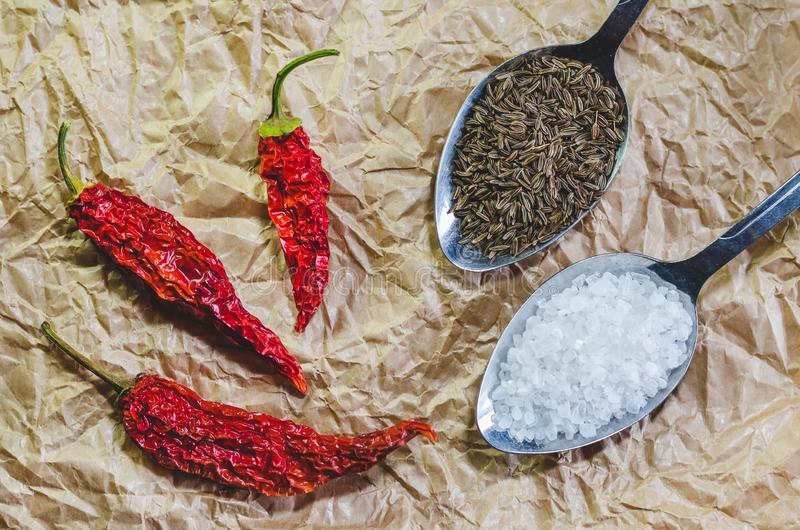 Poivrons secs d'un rouge ardent, cuillère avec du sel de mer et une cuillère avec des graines de cumin sur un papier de ouvrage image libre de droits