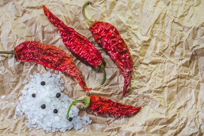 Poivrons secs d'un rouge ardent, sel de mer et poivre noir sur un papier de ouvrage photographie stock