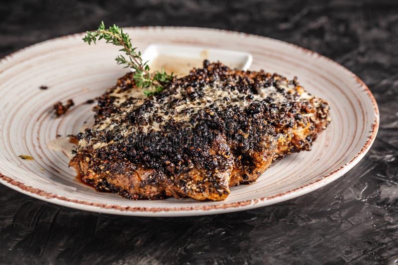 Pojęcie Amerykańska kuchnia Smażący, soczysty wieprzowina stek w czarnym pieprzu z serowym kumberlandem na białym ceramicznym nac obrazy royalty free