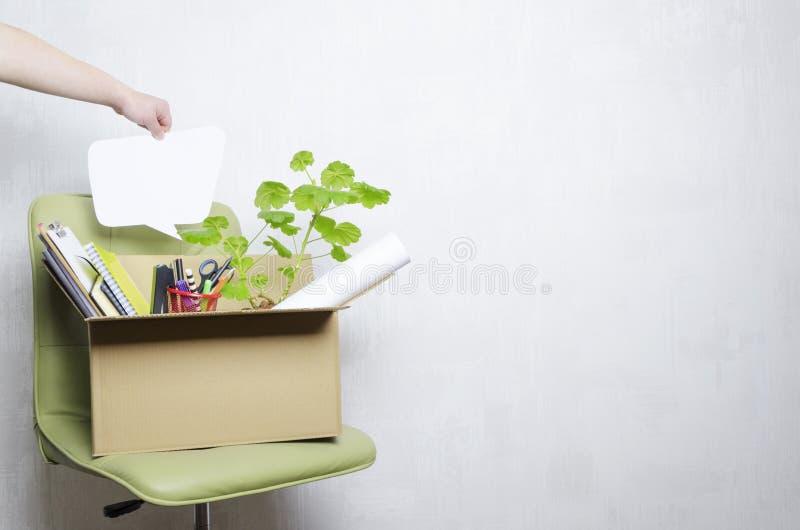 Pojęcie dymisji i pracownika myśli o to Kartonu pudełko z stacjonarnym na zielonym biurowym krześle obraz stock