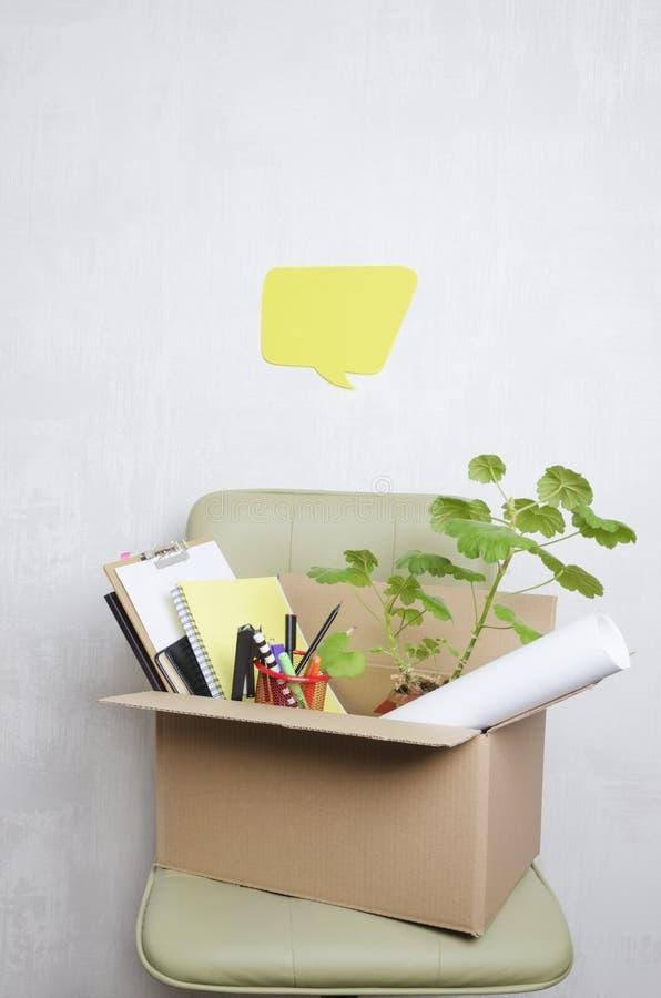 Pojęcie dymisji i pracownika myśli o to Kartonu pudełko z stacjonarnym na zielonym biurowym krześle zdjęcie royalty free