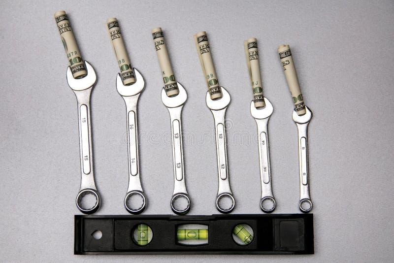 Pojęcie naprawianie waluta pieniądze i narzędzia Sześć wyrwania, waterpass i dolarów na szarość, obrazy royalty free