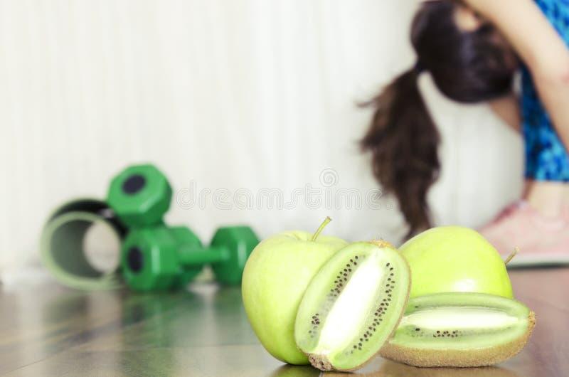 Pojęcie zdrowy posiłek po ćwiczeń Elastyczna kobieta robi rozciąganie rutynie i woli świeże owoc po treningu zdjęcia stock