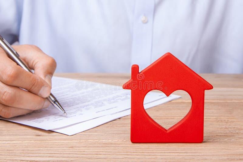Pojęcia domowy ubezpieczenie, czynsz lub zakup, Rewolucjonistka dom z sercem i mężczyzna podpisuje kontrakt fotografia royalty free