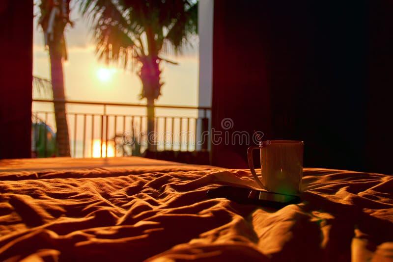 Pojęcia domowy wygodny w podróży Biały smartphone na łóżku w pogodnym wieczór i kubek zaświecamy od otwartego balkonowego drzwi L fotografia stock