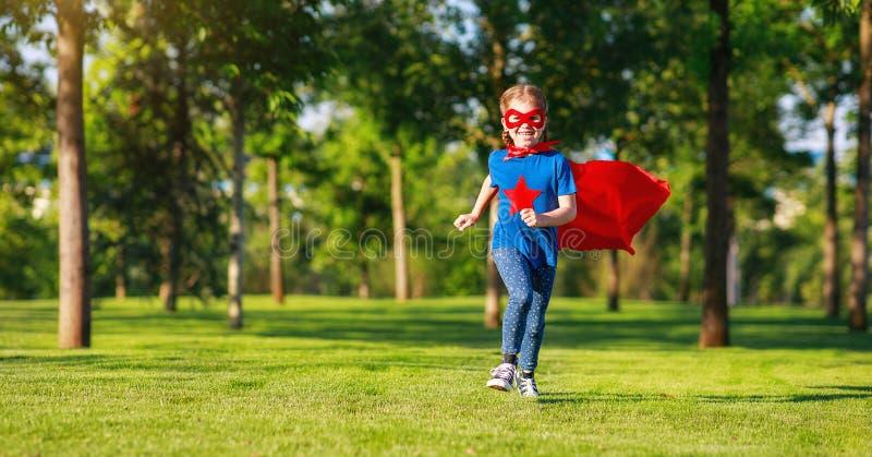 Pojęcia dziecka bohatera szczęśliwy bohater w czerwonej pelerynie w naturze zdjęcia royalty free