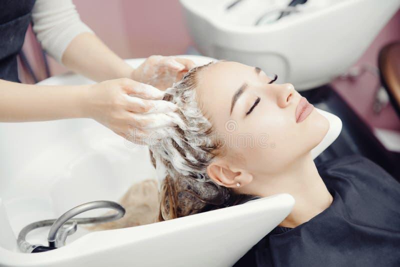 Pojęcia piękna salon Fryzjer myje włosy piękna blondynki dziewczyna pod klepnięciem w obmyciu zdjęcia stock
