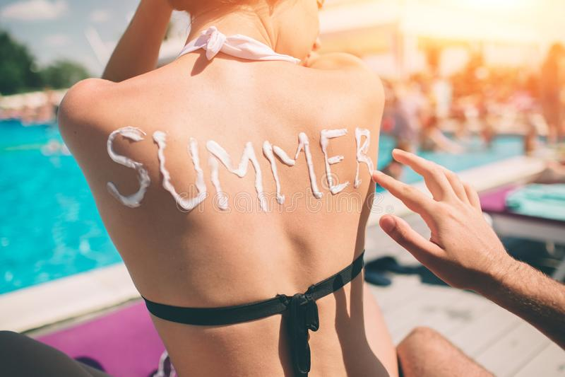 pojęcia tła ramy piasek seashells lato Mężczyzna pisze słowa lecie na kobiety ` s plecy Obsługuje stosować sunscreen na skórze dz obrazy royalty free