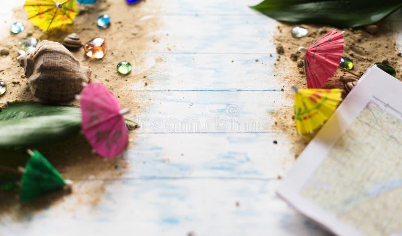 pojęcia tła ramy piasek seashells lato Parasole dla koktajli/lów na piasku na drewnianym tle z otoczakami zdjęcia stock