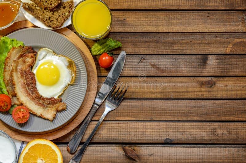 Pojęcie Angielski śniadanie: smażący jajko z bekonem, sokiem pomarańczowym i warzywami, bezpłatna przestrzeń dla teksta, odgórny  zdjęcia royalty free