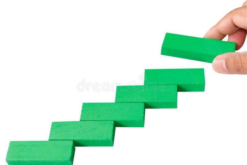 Pojęcie budynku sukcesu podstawa Ręka stawiająca zielona łamigłówka wo obraz stock