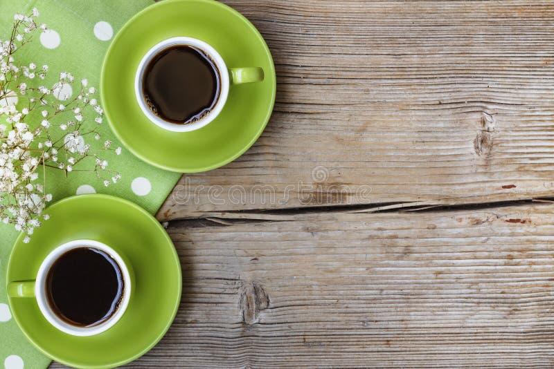 Pojęcie: data Dwa filiżanki kawowej na drewnianym tle, zielona polki kropki pielucha, odgórny widok, wieśniaka styl to walentynki fotografia stock